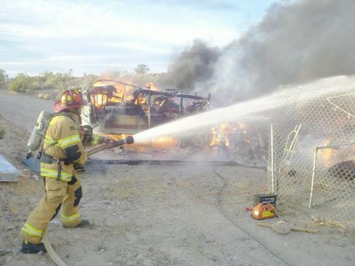 Fire Fighter using hose to control blaze
